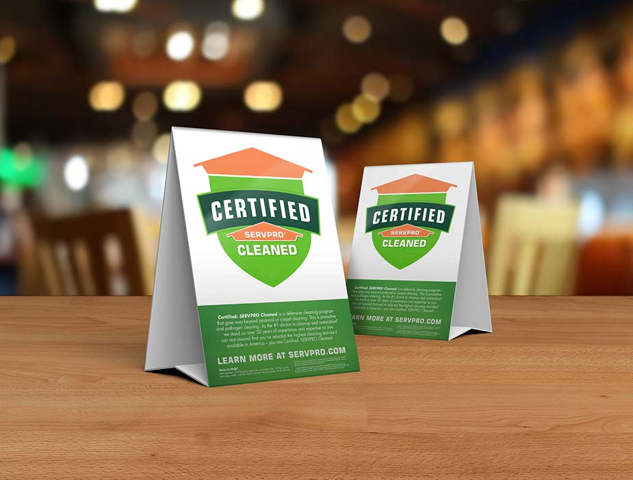 Table tent signs describing the Certified: SERVPRO Cleaned program on top of a wooden table.  Body: